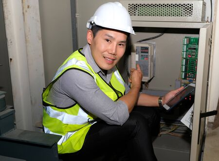 Electrician engineer point to the power generator and holding tablet at the control room of plant. Wearing safety vest and white helmet. Engineering and control room concept. Stock Photo