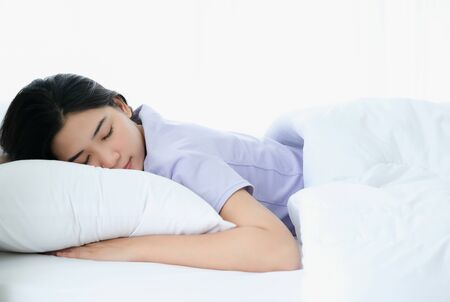 Young beautiful Asia woman sleeping and enjoy on the soft bed at the modern bedroom and feeling relaxing in the morning. Hugging soft white pillow. Resting, good dream and sleep concept. Stockfoto