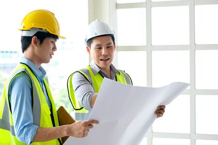 Two engineers man standing in front of the site. Left engineer holding blueprint diagram and right engineer point his hand to drawing diagram in blueprint. Engineering and construction concept.