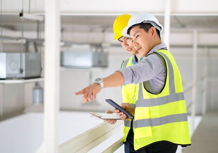 Two engineers man standing in the site. Engineer holding tablet and point to machine and explain detail of machine to other engineer. Engineering and construction concept. Standard-Bild