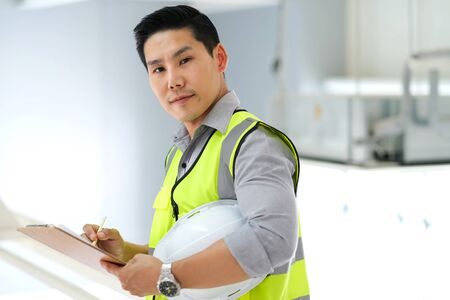 Senior engineer standing in the plant and  holding clipboard with copy space. Wearing safety vest and holding safety helmet. Feeling happy and fun on work. Engineering and design concept.