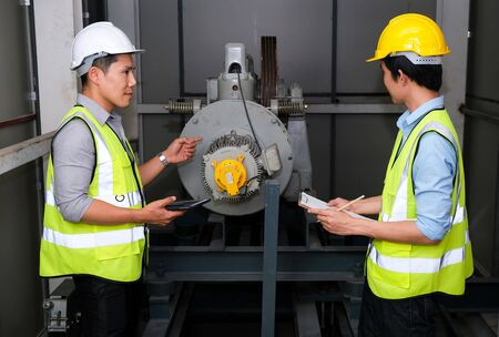 Senior engineer point to the lift motor and explain to junior engineer. Feeling fun on work at the control room of plant. Wearing safety vest and safety helmet. Engineering and control room concept.