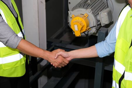 Senior engineer shake hand with junior engineer. They  feeling happy and success on work at the control room of plant. Wearing safety vest. Engineering and control room concept.