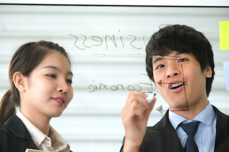 Asia young businessman write the idea on the transparent glass board in the modern office and explain to business women who is holding a brown notebook. Business and marketing concept.