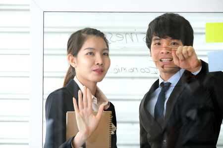Asia young businessman point to some word on the transparent glass board in the modern office and explain to business women who is holding a brown notebook. Business and marketing concept.