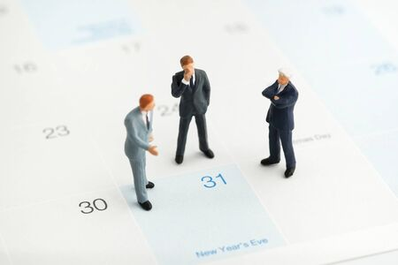 Miniature people : A group of businessmen standing on the white calendar and look at the end of new year (31 Dec) with copy space. He plan the new strategy for next year. Business, finance and concept