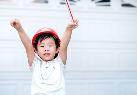 Young Asia boy in gray T shirt wearing a orange safety helmet and holding triangular reduction scales and raise hand up in the garden at home. Feeling happy and fun. Engineering and education concept.