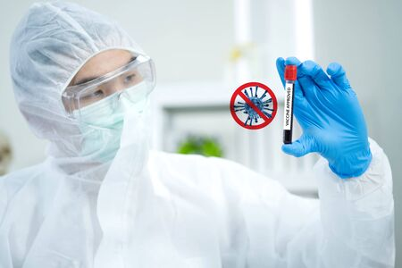 Scientists wear virus protection cloth and hold COVID 19 vaccine samples on his hand with coronavirus sign and blurred background. He looks at the test tube and success to win coronavirus