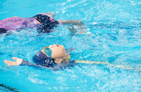 An Asia boy is swimming in the blue pool. Feeling fun and happy. Learning how to do backstroke swim. Summer children's sports activity with a friend. Learning and relaxation concept.