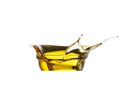 Automotive engine oil (lubricating oil, yellow liquid oil) splash and isolated on white background. High viscosity of base oil. Maintenance, service, and energy fuel concept.