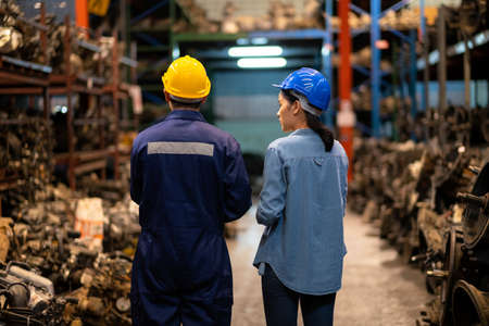Engineer man and administrator standing in the large warehouse. Keep the old machine parts. Both of them wearing a safety helmet. Used of vehicle part for recycling in the scrap yard garage. Stock Photo