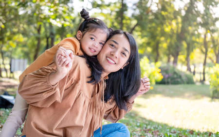Asia daughter riding her mother back in the park with copy space. Family outdoor activity. Mom and kid smile and looking at the camera. Enjoy, happiness, and relationship concept.