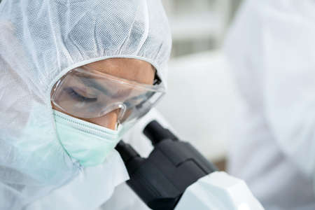 Scientists or doctor wearing personal protective and safety glass in the laboratory. Using a microscope and saw the tissue of virus. Research on the coronavirus vaccine to prevent COVID-19.
