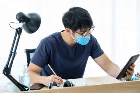 Asia man looking at smartphone or tablet and discuss with customer in the living room. Wearing hygiene mask and writing some message on notebook. Work at home. Business concept