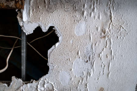 A huge hole of ceiling panels was damages from rainwater leakage in the abandoned house. Ceiling floor swelling and have fungi. Collapsed roof from natural disaster. Maintenance and repair concept Stock Photo