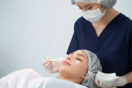 Cosmetologist or dermatologist doctor putting white cream with brush on pretty woman face in the beauty clinic. Facial massage treatment. A beautiful girl is put a rejuvenating on her face