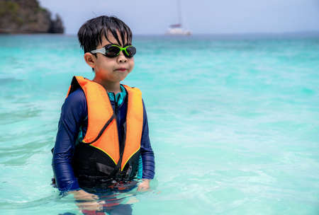 Asia child boy wearing goggles, swimming suit and life jacket standing in the sea at beach in Thailand with copy space. Summer vacation and holiday travel. Relaxation and happy in the water