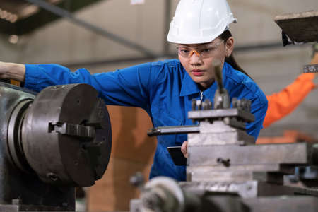 Portrait of engineer worker woman wearing uniform and PPE holding tablet and looking at machine in the factory. Preventive maintenance in factory. Industrial, technology and innovation concept. Stockfoto