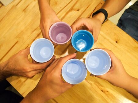 joining: Top view of people joining cups of water