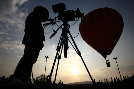 Silhouette of a TV cameraman against a sunset with hot air balloon  Stock Photo