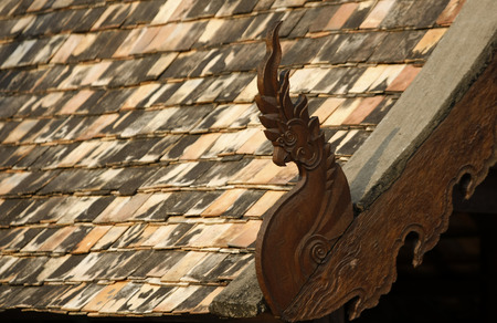 wood art design in font of the old clay roof photo