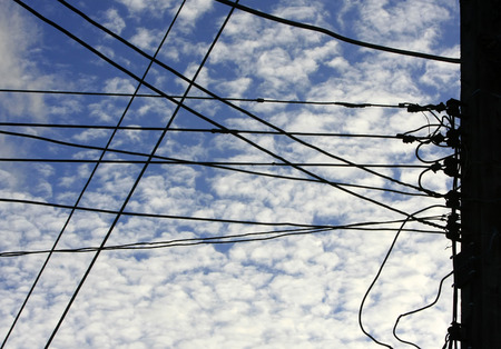 Silhouettes pole and wires against the blue sky with cloud Stock Photo