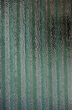 corrugated and translucent glass of window - green colored photo