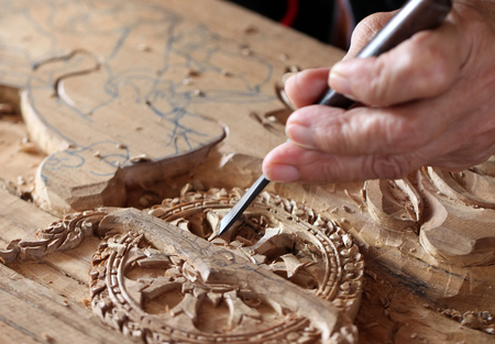 Hands of the craftsman carving a bas-relief.
