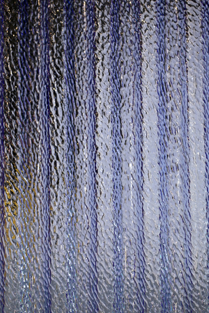 corrugated and translucent glass of window - Purple colored photo