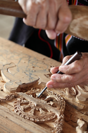 mastery: Hands of the craftsman carving a bas-relief.