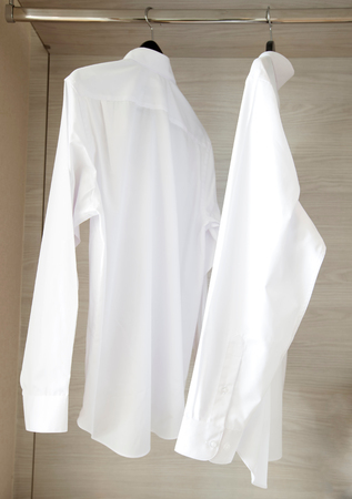 white shirts hanging on rack in built-in cupboard photo
