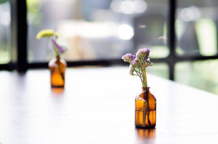 near: flower on wood table near window Stock Photo