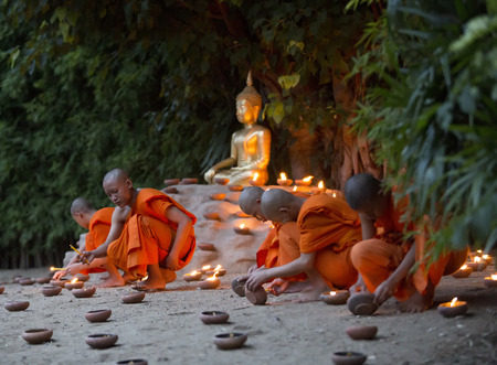 buddhism prayer belief: A monk, Asalha Puja Day - July 30 : Unidentified monks put candles on floor around image buddha in Asalha Puja Day on July 30, 2015 at Phan Tao temple in Chiang Mai, Thailand
