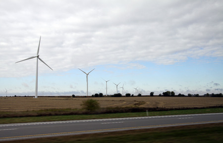 Wind turbine on the farm over the clouded sky near the road
