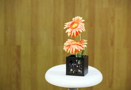 Gerbera in Vase black on white table.