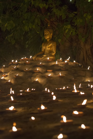 Buddhist monk fire candles to the Buddha with beautiful water reflection in Phan Tao Temple, Chiangmai, Thailand