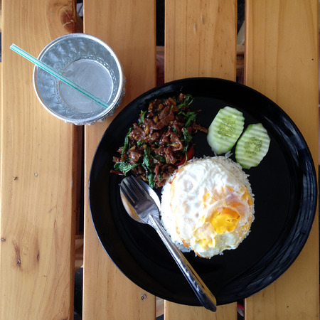 stir-fried beef and basil with rice and egg and water