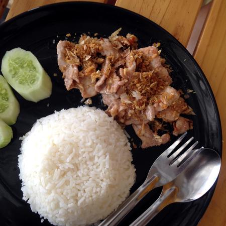 Thai style food, pork fried with crunchy garlic with cucumber