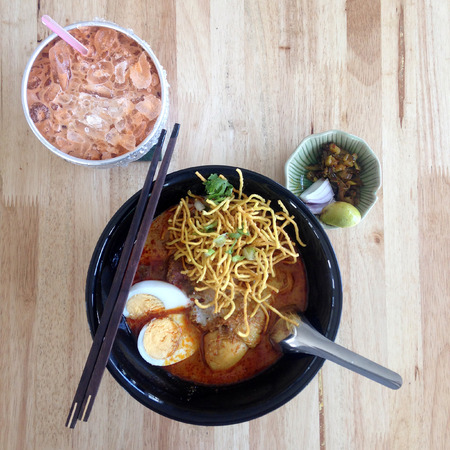 Chicken noodle with coconut milk and spicy soup , Thai northern food ( khao soi ) with Thai Ice Milk Tea Stock Photo