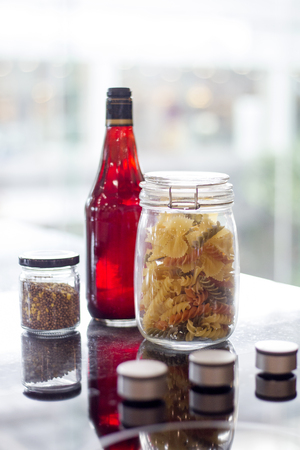 Pasta and spices in jars with Bottle on table in the kitchen