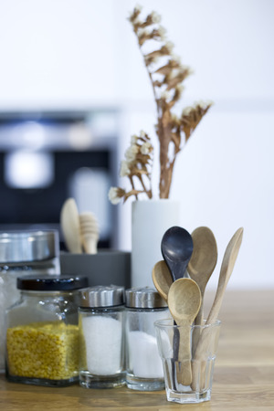 jars and spoons with garnish on wooden table Stock Photo