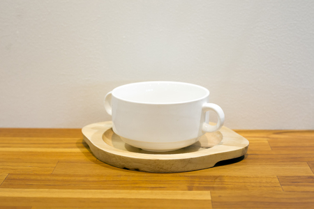Cup of coffee with wooden tray on wooden table background