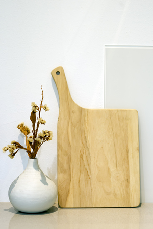 Wooden cutting board and white vase on the table