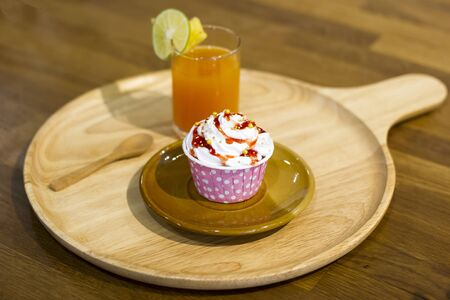 orange juice with cupcake on wooden tray on wooden table