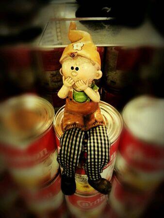 doll: Boy doll sitting on can