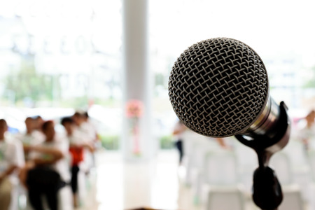 Microphone in concert hall or conference room with defocused person in background. Banco de Imagens