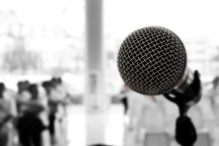 Microfoon in de concertzaal of conferentieruimte met onscherpe persoon op de achtergrond. Zwart en wit Stockfoto
