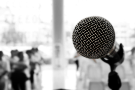 Microphone in concert hall or conference room with defocused person in background. Black and White