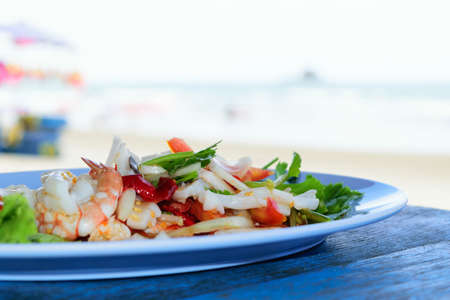 repast: Mixed seafood salad in dish on blue wood table