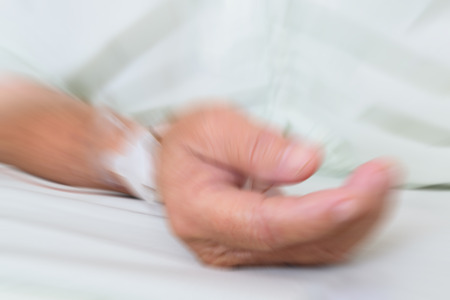 Blurred A patient in the hospital with saline intravenous, in Asian elderly man hand. Stock Photo